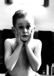 This 1990 publicity image originally released by 20th Century Fox, Macaulay Culkin portrays Kevin McCallister is a scene from the family comedy Home Alone.
