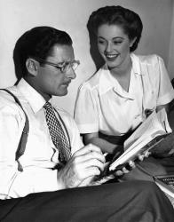 In this Aug. 25, 1945 file photo, Errol Flynn reads an amusing passage from a new novel to his leading lady, Eleanor Parker, on the set of Never Say Goodbye.