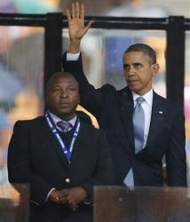 President Barack Obama waves standing next to the sign language interpreter at the memorial service for Nelson Mandela at the FNB Stadium in Soweto near Johannesburg, Dec. 10, 2013.