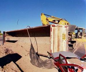 This 2002 photo provided by plaintiff's attorney Vigil Law Firm shows a tractor-trailer that overturned, burying it in sand and suffocating the woman inside, in Albuquerque, N.M.