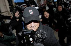 In this Wednesday, Dec. 17, 2008 photo, Bernard Madoff enters his house through a crowd of cameras in New York.