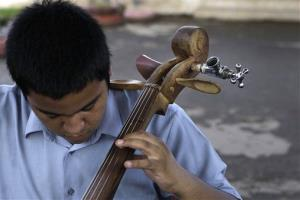 In this Dec. 11, 2012 photo, a young musician tunes his cello.