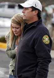 A father picks up his daughter at a church where students from nearby Arapahoe High School were evacuated to after a shooting on the Centennial, Colo., campus Friday, Dec. 13, 2013.