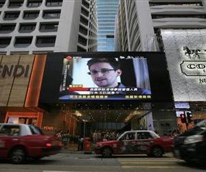 A large television screen shows a news report on Edward Snowden outside a shopping mall in Hong Kong on Sunday, June 23, 2013.