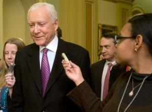 In this Dec. 31, 2012 file photo, Sen. Orrin Hatch, R-Utah, center, fields questions from reporters as he walks on Capitol Hill in Washington.
