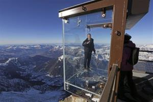 In this photo taken on Tuesday, Dec. 17, 2013, Mathieu Dechavanne, head of the Compagnie du Mont Blanc which runs the new attraction, stands in a glass cage named 'Pas dans le Vide' (Step into the Void) at the top of the Aiguille du Midi peak (3842-meters high or 12,...