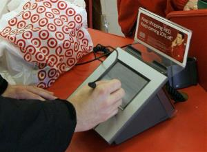 In this file photo, a customer signs his credit card receipt at a Target store.