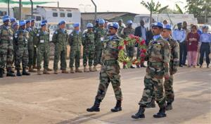 In this photo released by the United Nations Mission in South Sudan (UNMISS), U.N. peacekeepers walk to lay flowers on coffins of their two colleagues who were killed on Thursday, at a memorial service held in the UNMISS compound in Juba, South Sudan, Saturday, Dec. 21, 2013. The U....