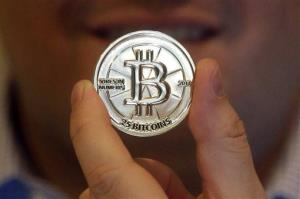 In this April 3, 2013 photo, Mike Caldwell, a 35-year-old software engineer, holds a 25 Bitcoin token at his shop in Sandy, Utah.