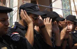 Egyptian policemen pray during a military funeral for policemen who were killed during Wednesday's clashes in Cairo, Egypt, Thursday, Aug. 15, 2013.