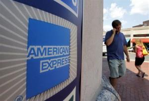 In this Tuesday, July 19, 2011, file photo, passersby walk past an American Express logo near the entrance to a bank in Cambridge, Mass..