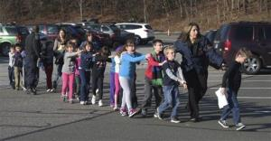 In this Dec. 14, 2012, file photo provided by the Newtown Bee, Connecticut State Police lead a line of children from the Sandy Hook Elementary School in Newtown, Conn.