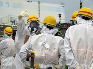 In this Wednesday, Sept. 25, 2013 photo, experts confer with a Tokyo Electric Power Co. official, center, as they inspect the crippled Fukushima Dai-ichi nuclear power plant.