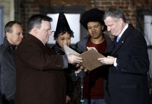 City Clerk Michael McSweeney assists Bill de Blasio as he signs the oath of office.