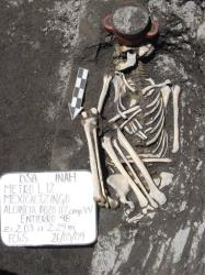 The skeleton of a person lies next to an incense holder after it was found during excavations for Line 12 of Mexico City's subway/
