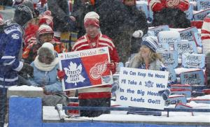 Hockey fans hold up signs during the first period of the Winter Classic outdoor NHL hockey game between the Detroit Red Wings and the Toronto Maple Leafs at Michigan Stadium in Ann Arbor, Mich., Wednesday, Jan. 1, 2014.
