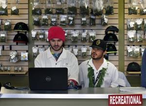 Employees David Marlow, right, and Chris Broussard work behind sales counter inside Denver's Medicine Man marijuana store.