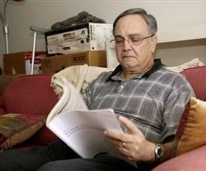 Howard Kraft looks over healthcare information in his home in Lincolnton, NC, Dec. 30, 2013. Kraft has a painful spinal problem, and is only able to get coverage because of the law.
