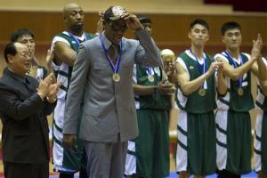 Dennis Rodman tips his hat as U.S. and North Korean basketball players applaud at the end of an exhibition basketball game at an indoor stadium in Pyongyang, North Korea on Wednesday, Jan. 8, 2014.