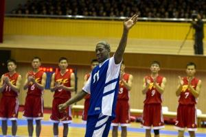 Dennis Rodman waves to North Korean leader Kim Jong Un, seated above in the stands, before an exhibition basketball game with US and North Korean players in Pyongyang yesterday.