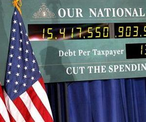 The shadow of Mitt Romney, is seen on a representation of the National Debt Clock as he speaks at a town hall meeting in Kalamazoo, Mich., Feb. 24, 2012.