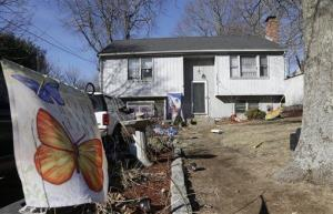A banner is attached to a stake in front of a homem Jan. 13, 2014, in Franklin, Mass., where authorities say a brother and sister have died after apparently getting trapped inside a hope chest.