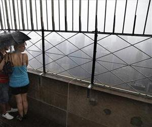 Tourists look over a foggy and rainy New York City from the observation deck of the Empire State Building in New York, Wednesday, July 3, 2013.
