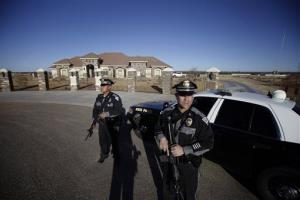Two New Mexico State Police officers stand guard holding semi-automatic rifles outside the home of Mason Campbell, the alleged shooter at Berrendo Middle School in Roswell, NM, Tuesday Jan. 14, 2014.