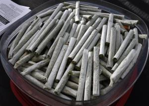 In this Oct. 2, 2013 photo, joints are piled into a container during a free pot giveaway during an anti-pot tax rally, in Denver.