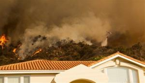 A firefighting helicopter makes a water drop behind a home north of the San Gabriel Valley community of Glendora, Calif.