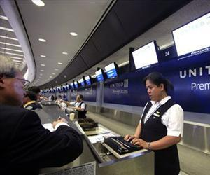 In this Wednesday, July 13, 2011, file photo, ticket agent Dee Manzon helps a customer at United Airlines premier access check-in counter at San Francisco International Airport.