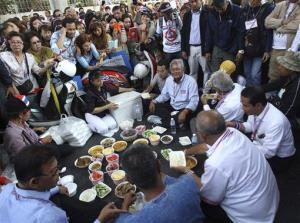 Anti-government protest leader Suthep Thaugsuban, center, sits with others for lunch during a protest rally, Tuesday, Jan. 21, 2014, in Bangkok, Thailand.