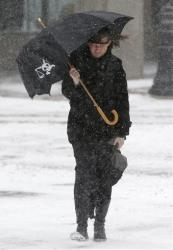 File photo of a woman bracing herself from the wind and snow.