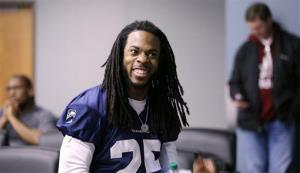 Seattle Seahawks' Richard Sherman smiles as he waits in the back of an interview room for his turn to speak at an NFL football news conference Jan. 22.
