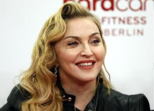 In this Thursday, Oct. 17, 2013 file photo, Madonna smiles during her visit at the Hard Candy Fitness center in Berlin.
