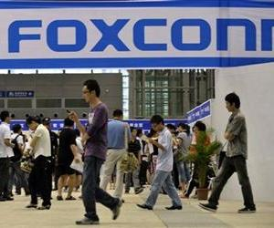 In this file photo taken on May 22, 2010, visitors to a job fair walk past the Foxconn recruitment area in Shenzhen in south China's Guangdong province.