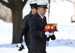 Penfield Fire Chief Chris Ebmeyer arrives at the funeral of Tyler Doohan. He's carrying the fire helmet the company made to honor 9-year-old Tyler.