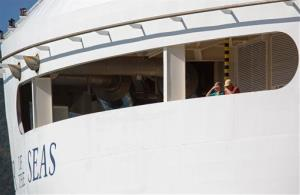Passengers look out from the Royal Caribbean International's Explorer of the Seas cruise ship, docked at Charlotte Amalie Harbor in St. Thomas, US Virgin Islands, Sunday, Jan. 26, 2014.
