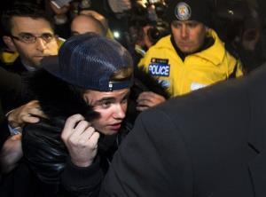 Canadian musician Justin Bieber is swarmed by media and police officers as he turns himself into city police for an expected assault charge, in Toronto, on Wednesday, Jan. 29, 2014.