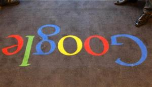 In this Dec. 6, 2011 file photo, the Google logo is seen on the carpet at Google France offices, in Paris.