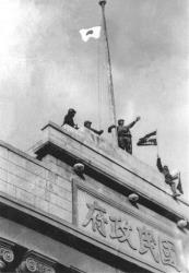 In this Dec. 1937 file photo Japanese soldiers hoist their flag from the roof of the central government building after they seized Nanking in the Second Sino Japanese War.