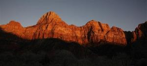 This Jan. 20, 2011 file photo shows shadows creeping up on sandstone cliffs glowing red as the sun sets on Zion National Park near Springdale, Utah.