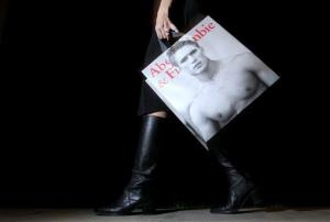 In this Nov. 14, 2011 photo, a shopper carries her Abercrombie & Fitch purchase, in Phoenix.
