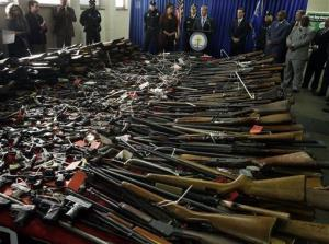 Guns cover tables in front of Camden Mayor Dana Redd, center left, and New Jersey Attorney General Jeffrey Chiesa, center at podium, after a gun buyback event.