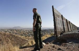 A US Border Patrol agent looks out over Tijuana, Mexico, behind, along the old border wall along the US - Mexico border, where it ends at the base of a hill in San Diego.