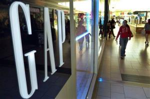 Shoppers walk by the GAP store at a shopping mall in Peabody, Mass.