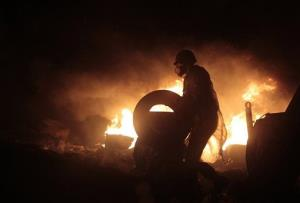 An anti-government protester holding a tire is silhouetted against flames during a clash with riot police in Kiev's Independence Square.