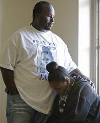 Martin Winkfield places his arm around his wife Nailah Winkfield, mother of 13-year-old Jahi McMath, as they wait outside a courtroom Friday, Jan. 3, 2014.