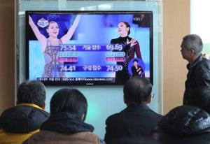 People watch a TV news report with images of Russia's Adelina Sotnikova, left, and South Korea's Yuna Kim during the 2014 Winter Olympics, in Seoul, South Korea, Friday, Feb. 21, 2014.