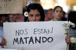 An opposition demonstrator holds a poster that reads in Spanish They are killing us outside the Venezuelan Military Industries (CAVIM) in Caracas Thursday.